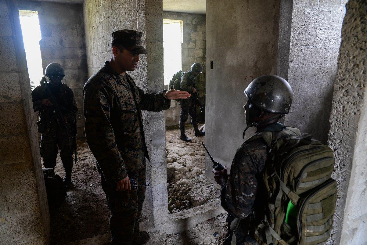 U.S. Marine Staff Sgt. Jorge Avila, instructor, gives directions to a Guatemalan Marine during a training exercise March 9, 2016, Guatemala. The Guatemalan marines partnered with trainers from a U.S. Marine Security Cooperation Team to learn basic infantry maneuvers and how to conduct squad-level movements in an urban environment. (U.S. Air Force photo by Staff Sgt. Westin Warburton/RELEASED)