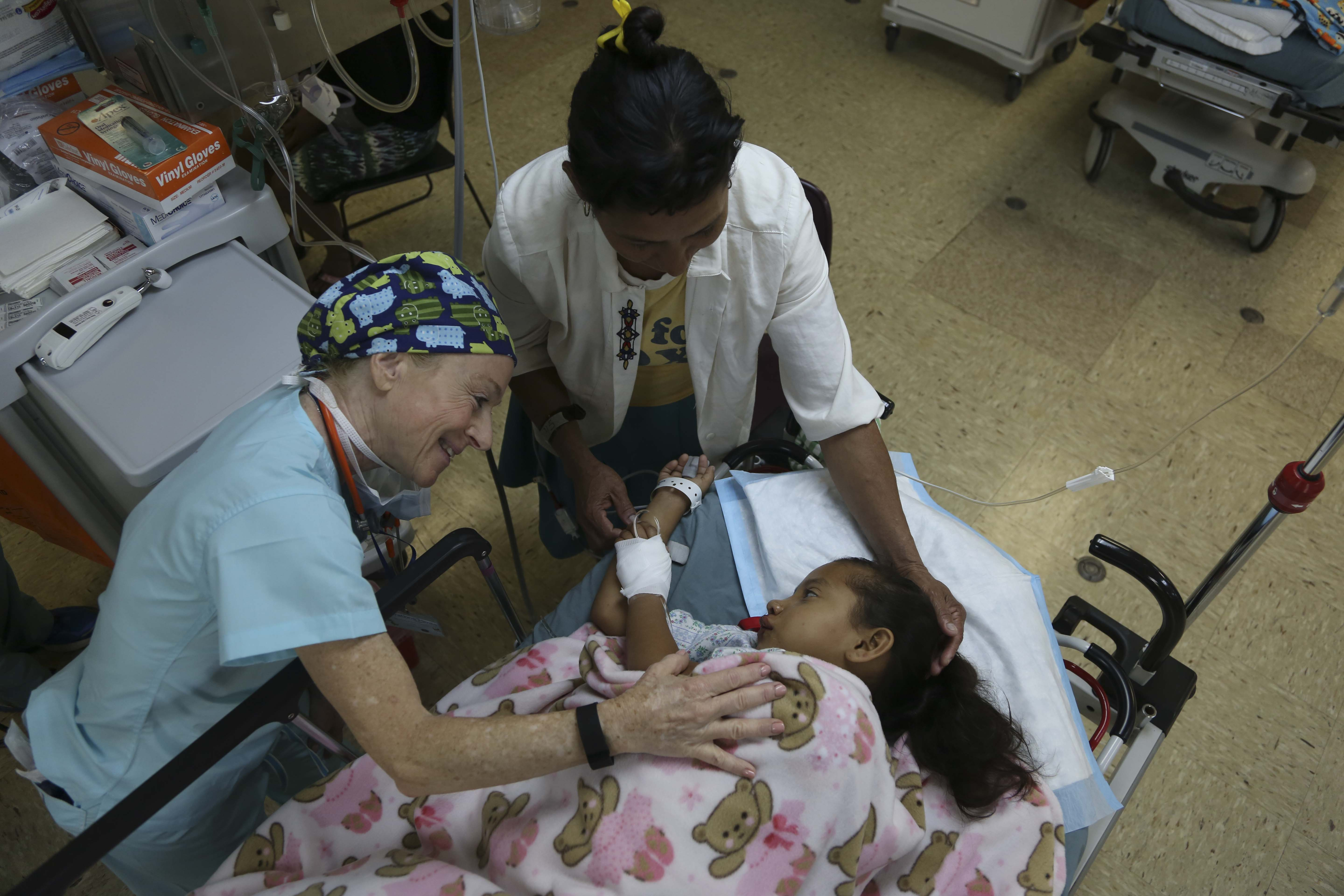 Dr. Judith Brill, a physician volunteering with the non-governmental organization Operation Smile, comforts a Nicaraguan patient in the post-operating room aboard USNS Comfort during Continuing Promise 2015.